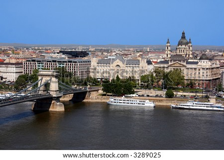 Beautiful view on Hungarian capital city, Budapest. Includes: Danube river, Chain Bridge (Szechenyi), St. Istvan basilica, ships and other buildings. - stock photo