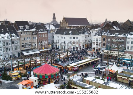 Beautiful view on the city of Maastricht in the Netherlands with a Christmas market on its main square on a snowy winter day - stock photo