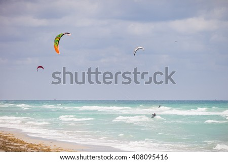 Beautiful view on the ocean beach with colorful kites. Cloudy day by the sea. Ocean coast. Vacation travel concept - stock photo