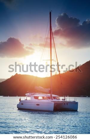 Beautiful view to catamaran in Seychelles bay at sunset - stock photo