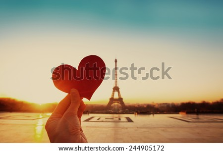 beautiful vintage card from Paris, Eiffel tower and hand with paper heart at sunrise - stock photo