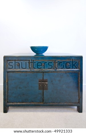 Beautiful vintage cupboard with three drawers and ceramic bowl on top - stock photo