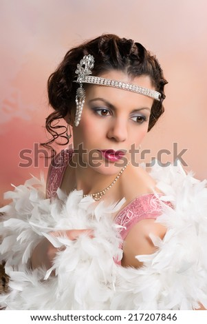 Beautiful vintage 1920s lady wearing a headband and white feather boa - stock photo