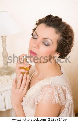 Beautiful vintage 1920s woman applying perfume in her boudoir - stock photo