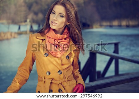 Beautiful vintage woman standing in a park in autumn - stock photo