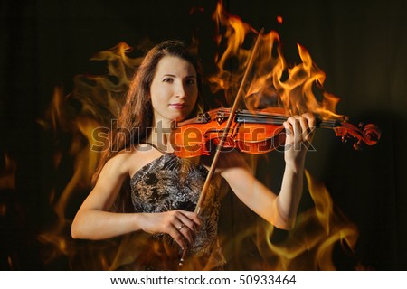 Beautiful violinist in flame playing on black