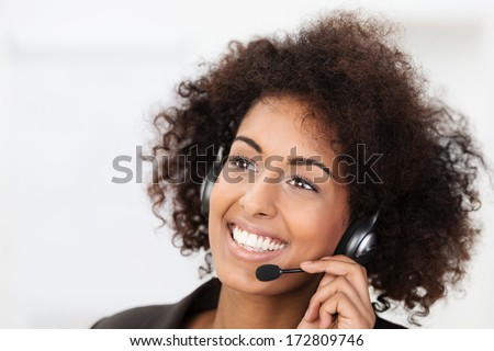 Beautiful vivacious young African American client services, call centre operator or receptionist smiling a warm friendly natural smile as she listens to a client speaking on her headset - stock photo