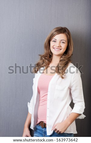 Beautiful vivacious young teenage girl posing in a relaxed manner with her hand in her jeans pocket smiling at the camera - stock photo