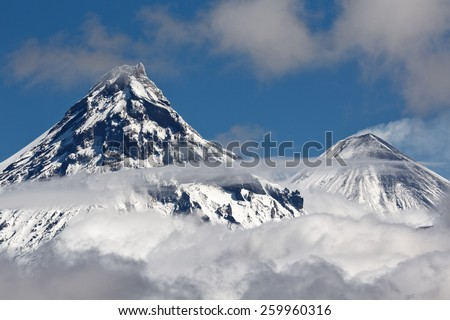 Beautiful volcanic landscape: view on cone Kamen Volcano and erupting active Klyuchevskoy Volcano above the clouds. Russia, Far East, Kamchatka, Klyuchevskaya Group of Volcanoes.