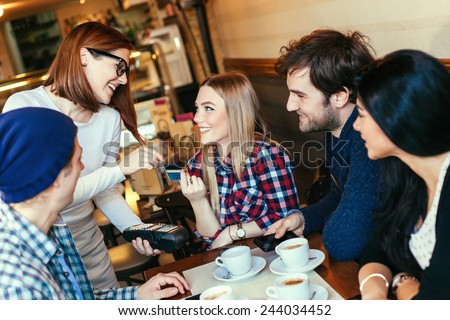 Beautiful Waitress Charging Customers Bill With A Credit Card Terminal - stock photo