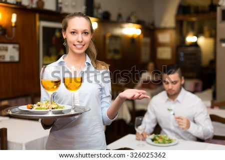 Beautiful waitress with shining smile serving clients in a restaurant with a tray in her hand - stock photo