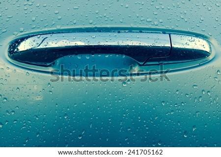 beautiful water drops on handle of car door - stock photo