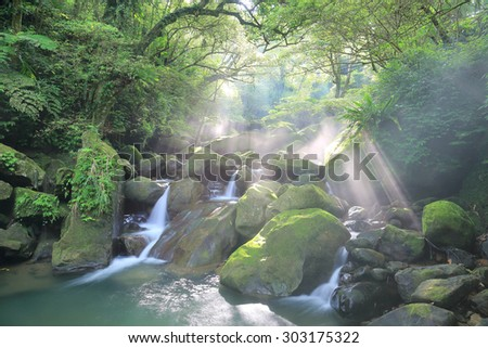 Beautiful waterfall in jungle ~ Refreshing cascades in a mysterious forest with sunlight shining through lush greenery ~ River scenery of Taiwan  - stock photo