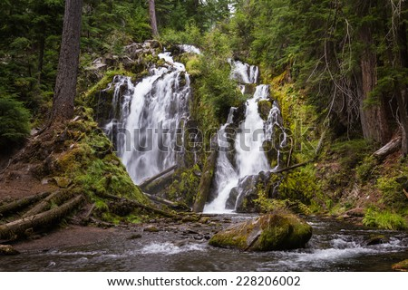 beautiful waterfall in southern Oregon with lush green plant life and rushing waters - stock photo