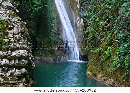 Beautiful waterfall in the forest among the gorge - stock photo