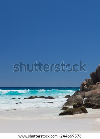 beautiful waves crashing against large granite rocks on the Seychelles with white sand beach - stock photo