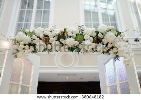 Beautiful wedding arch for marriage decorated with lace fabric and flowers. White decor for bride and groom. Colorful decoration for celebration. Beauty bridal interior - stock photo