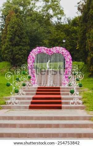 Beautiful wedding arch with pink orchid standing on the steps of - stock photo