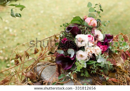 Beautiful wedding boho bouquet of red and pink flowers and greens. - stock photo