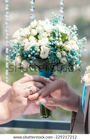 Beautiful wedding bouquet in bride's and fiance's hands - stock photo
