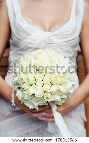 Beautiful wedding bouquet in hands of the bride.  WARNING! Focus only on the  wedding bouquet - stock photo