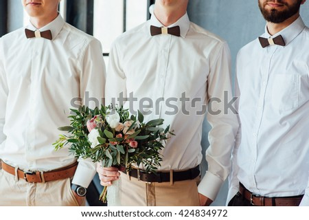 Beautiful wedding bouquet in hands of the groom. with his friends - stock photo