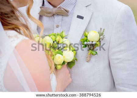 Beautiful wedding bouquet in rustic style with yellow peonies. bride with bouquet. the groom's beautiful boutonniere. - stock photo
