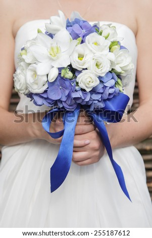 Beautiful wedding bouquet of hydrangea, eucharis and eustoma flowers in hands of the bride - stock photo