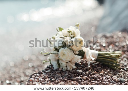 beautiful wedding bouquet of white roses lying on the pebbles on the beach