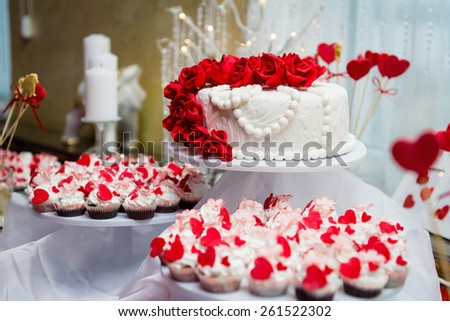 Beautiful wedding cake and cupcakes in decoration - stock photo
