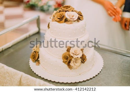 Beautiful wedding cake decorated with beige and peach-colored roses - stock photo