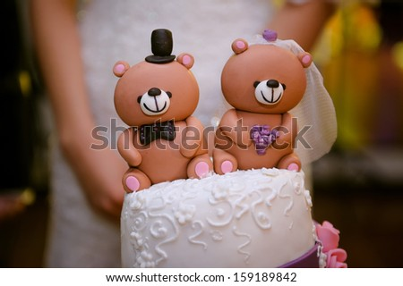 beautiful wedding cake with a teddy bear at the top - stock photo