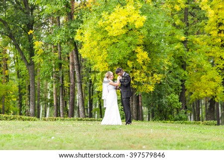 Beautiful wedding couple in park. They kiss and hug each other - stock photo