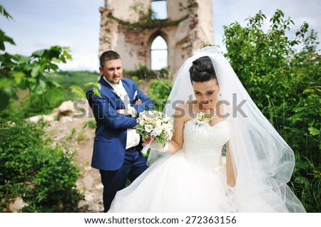 beautiful wedding couple near ruins tower of old castle - stock photo