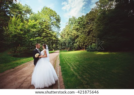 beautiful wedding couple. The bride and groom in wedding day walking outdoors in spring nature. Bridal couple Newlywed happy woman and man embracing a green park. - stock photo