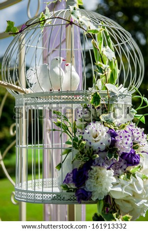 Beautiful wedding decoration. Birdcage with artificial white birds and flowers - stock photo