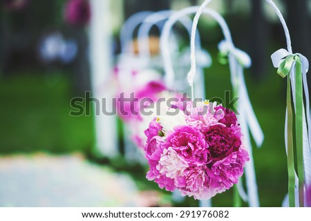 Beautiful wedding decorations in the form of flowers that hang on a chair