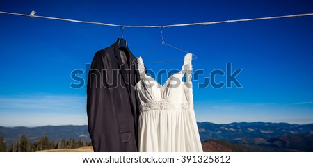 Beautiful wedding dress and suit hanging on hanger. Amazing mountain landscape background
