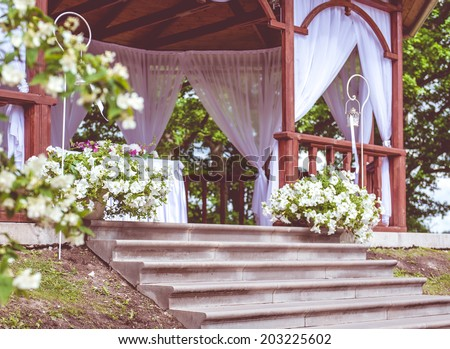 Beautiful wedding gazebo with flower decoration - stock photo