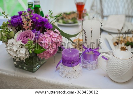 Beautiful wedding reception table arrangement, tableware and white and purple flowers