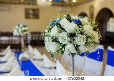 Beautiful wedding restaurant for marriage. White-Blue decor for bride and groom. Colorful decoration for celebration. Beauty bridal interior. Bouquet, food and flowers in hall - stock photo