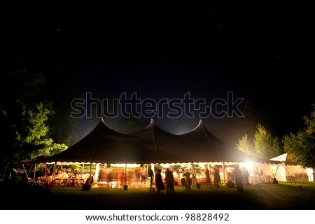 Beautiful wedding tent set up for an outdoor reception. This is a long night exposure, there is blur under the tent showing activity - stock photo