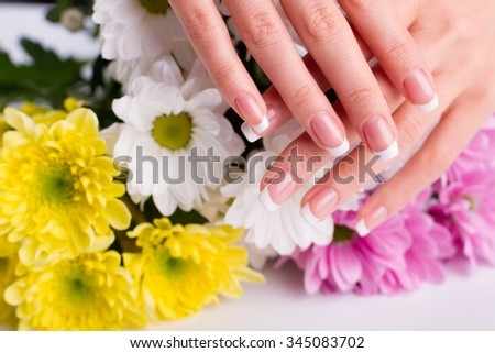 Beautiful well-groomed female fingers with manicure. Women's hands on the background of flowers.