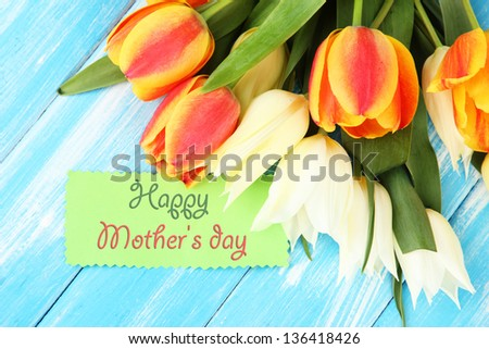 Beautiful white and orange tulips on color wooden background - stock photo