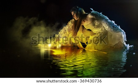 Beautiful white angel is standing in the magic water. - stock photo