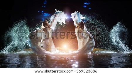 Beautiful white angels are dancing in the water drops. - stock photo