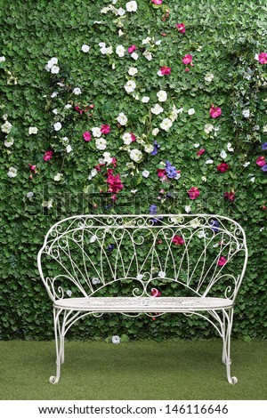 Beautiful white bench next to green hedge with small flowers. - stock photo