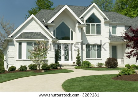 Beautiful white brick home featuring a modern architectural design with large windows and a circular driveway. The yard is completed with formal landscaping. - stock photo