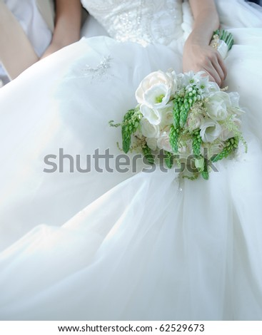 Beautiful white bridal bouquet with large space for your text on wedding dress - stock photo