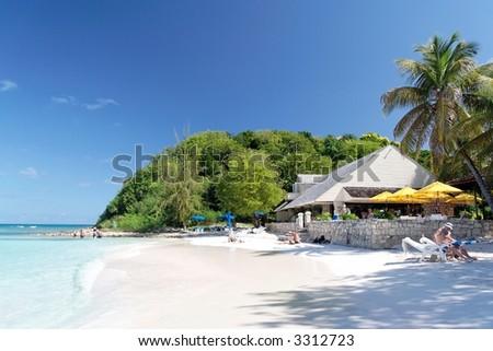 Beautiful white caribbean beach with restaurant - stock photo